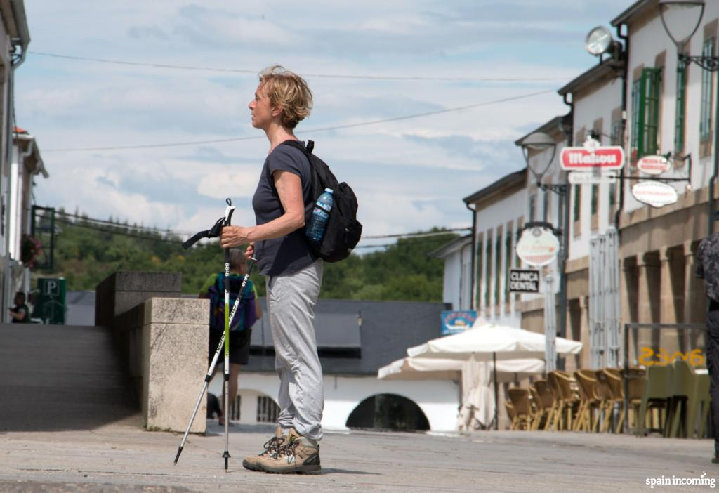 Perfect pilgrim with walking sticks, trekking shoes, small backpack